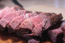 Closeup of beef sirloin tip roast cut up into steaks